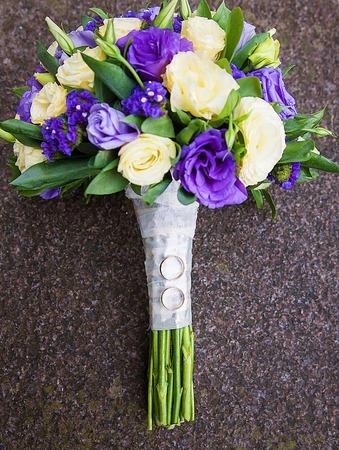 Foto de bridal bouquet of purple and beige colors and wedding rings - Imagen libre de derechos