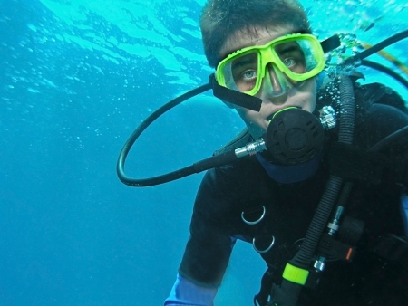 A young male scuba diver underwater in full gear