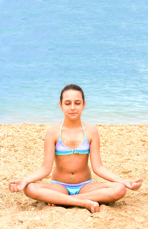Photo pour beautiful young teenager girl practice yoga meditation summer sea beach - image libre de droit