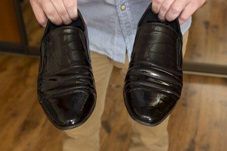 Photo pour Classic black patent leather male shoes in hands of man - image libre de droit