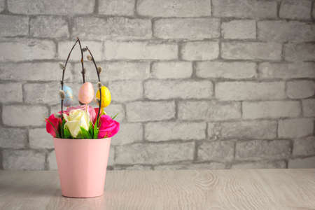 Photo pour Flowers, willow twigs and easter eggs in basket in as Easter gift - image libre de droit