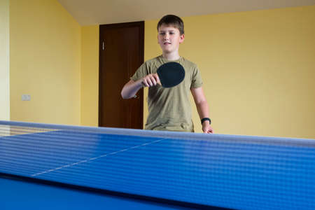 Photo pour An 11-year old teenager with a tennis racket in his hands is playing table tennis. Sport lifestyle. - image libre de droit