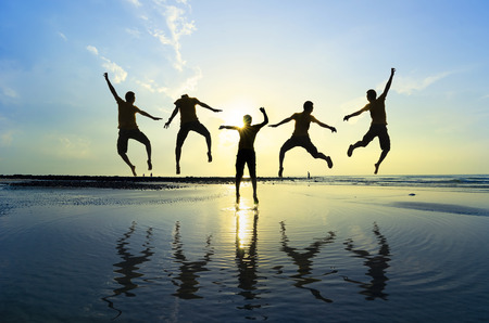 Photo for Silhouette of friends jumping over sun rising up - Royalty Free Image
