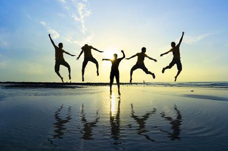 Foto de Silhouette of friends jumping over sun rising up - Imagen libre de derechos