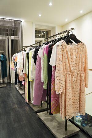 Photo pour colorful Women's dresses on hangers in a fashion store. Shop stylish clothes, close-up. - image - image libre de droit