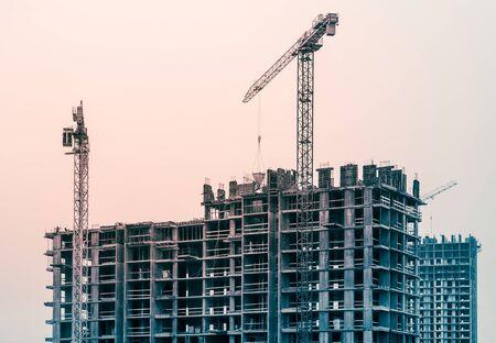 Photo pour Construction crane and building construction site tinted in blue and red colors - image libre de droit