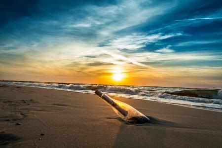 Photo pour SOS message in a bottle on the beach - image libre de droit