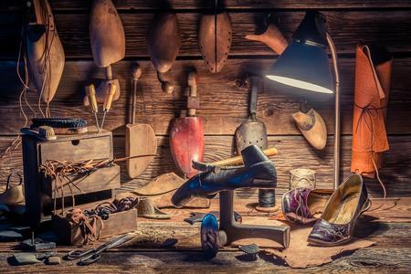 Photo pour Vintage shoemaker workplace with brush and shoes - image libre de droit