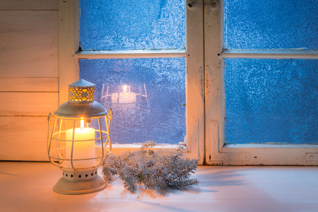 Photo pour Blue window at night and burning candle for Christmas - image libre de droit