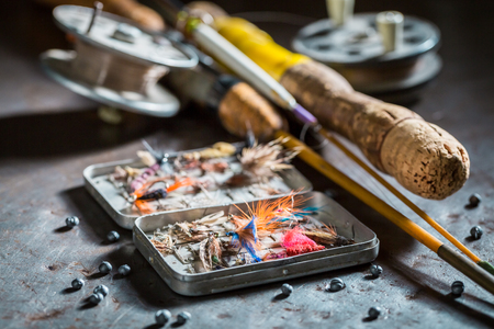Photo pour Fishing tackle with fishing flies and rods on metal table - image libre de droit