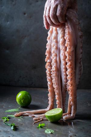 Foto de Freshly caught octopus holding in hand and lime - Imagen libre de derechos