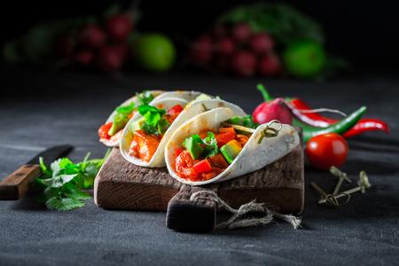 Foto de Tacos with spicy sauce and coriander on concrete table - Imagen libre de derechos
