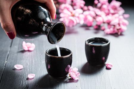 Photo pour Pouring sake to dark ceramics on black table - image libre de droit