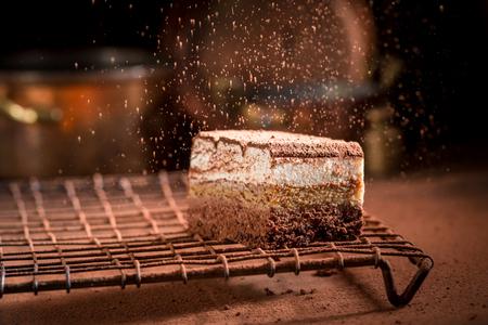 Foto de Tiramisu cake on metal cooling grid falling cocoa powder - Imagen libre de derechos