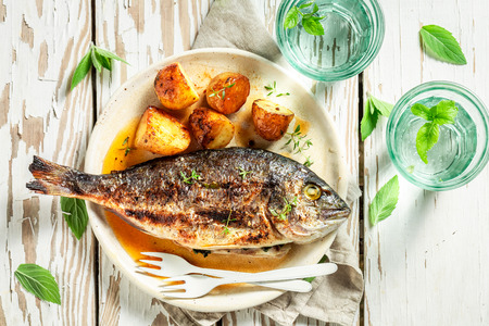 Photo pour Top iew of grilled potatoes and seabream with tomatoes - image libre de droit