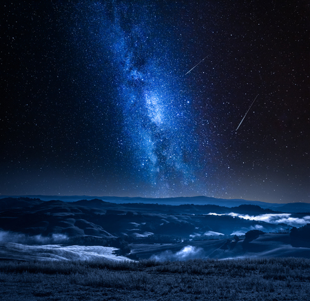 Photo pour Milky way with falling stars and foggy valley in Italy - image libre de droit