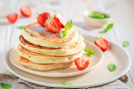 Photo pour Delicious american pancakes with powdered sugar and sweet strawberries - image libre de droit