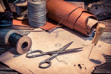Photo pour Closeup of vintage cobbler workplace with shoes, laces and tools - image libre de droit
