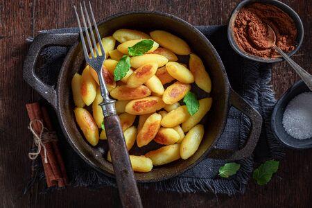 Photo pour Tasty potato dumplings with cinnamon, sugar and mint leaves - image libre de droit