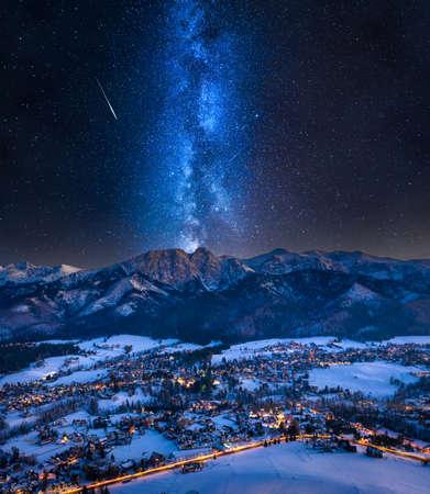 Foto de Milky way over illuminated Zakopane city in winter. Night hiking in the mountains - Imagen libre de derechos