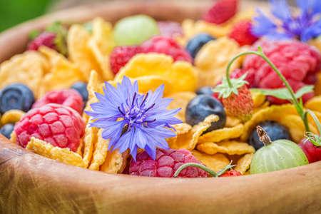 Foto für Flowers and fruits with cornflakes. Healthy and slimming breakfast in garden. - Lizenzfreies Bild