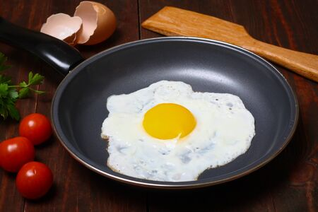 Pan of fried eggs, with cherry-tomatoes and parsley on a wooden table surfaceの写真素材