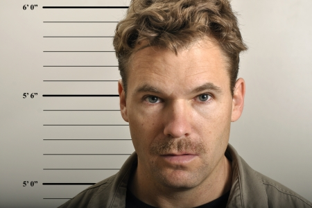Police mug shot of scruffy man with mustache