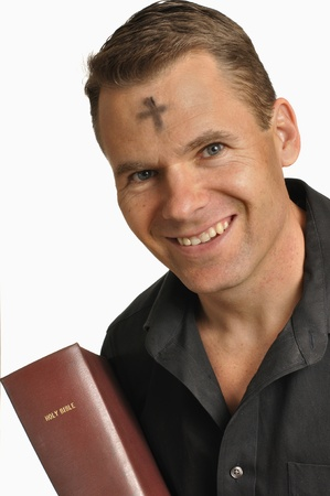 Smiling man with mark of ashes on forehead holds holy Bible