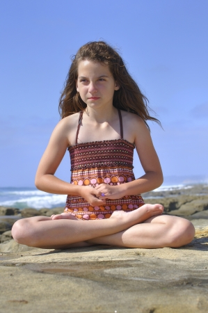 Young girl performs Padmasana yoga lotus pose on rocky shore in La Jolla, California