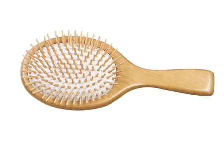 Closeup of massaging hair brush with natural wood handle, base, and pins isolated on white background