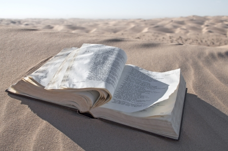 Old Christian Bible lies open in desert sand dunes with pages flapping in wind