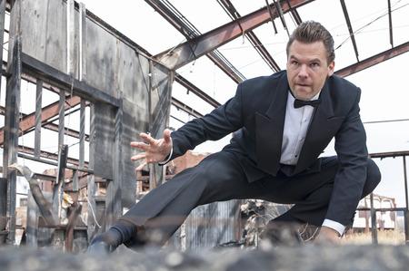 Foto de Handsome tough Caucasian man in black tuxedo poses in action stunt scene in destroyed warehouse - Imagen libre de derechos
