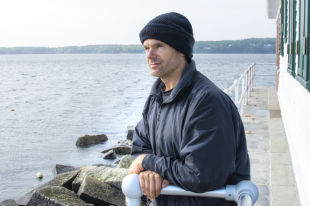 Handsome Caucasian man dressed in jacket and black cap leans against railing of lighthouse at end of breakwater in Rockland Maine as he gazes peacefully into the distant ocean