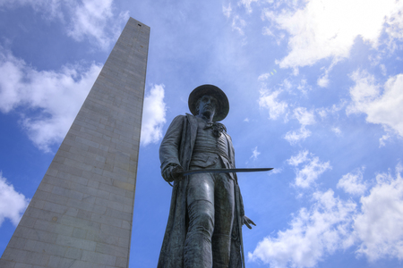 Low angle wide angle of Colonal William Prescott and Bunker Hill monument reaching high in the sunny sky of the Freedom Trail in Boston, Massachusetts