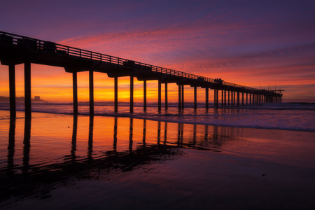 Brilliant evening sunset and silhouette of Scripps Pier with reflections on La Jolla Shores beach in California