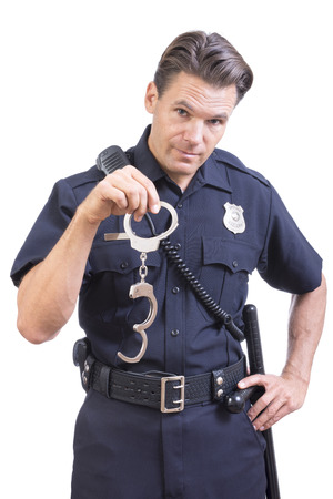 Handsome Caucasian police officer dangles pair of handcuff restraints in one hand as a warning on white background