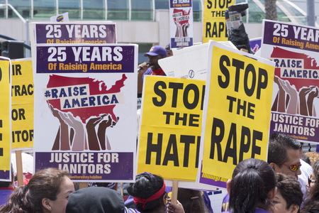 SAN DIEGO, USA - MAY 27, 2016: Protesters hold signs supporting wage increases for janitors while a supporter speaks to the crowd outside a Donald Trump rally at the San Diego Convention Center.