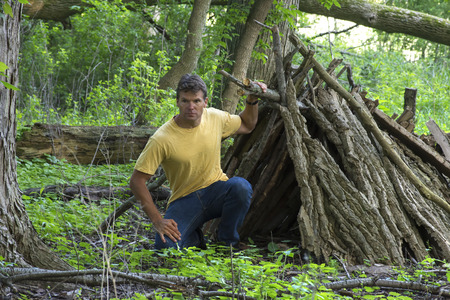 Survivor man kneels next to opening of small primitive A-frame survival shelter made of logs in lush forest