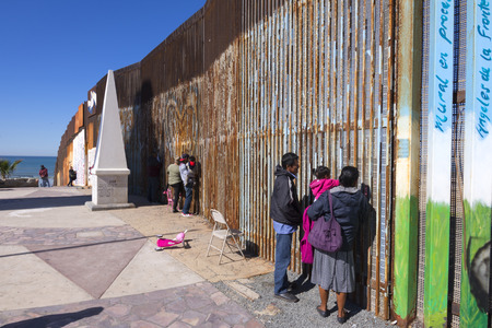 Photo for PLAYAS DE TIJUANA, MEXICO - JANUARY 28, 2017: Mexican families living in Tijuana visit with family members living in the United States by meeting at the border wall in Playas de Tijuana on a sunny winter Saturday morning. - Royalty Free Image