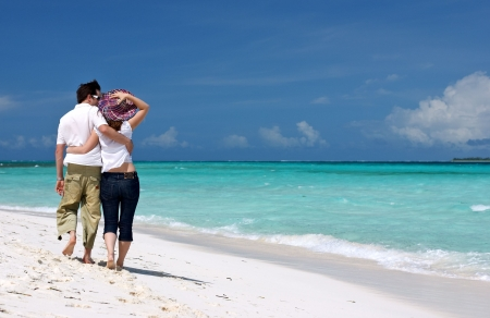 Loving couple walking along tropical beach