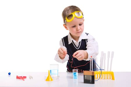 Young boy performing experiments with battery and small lamp.