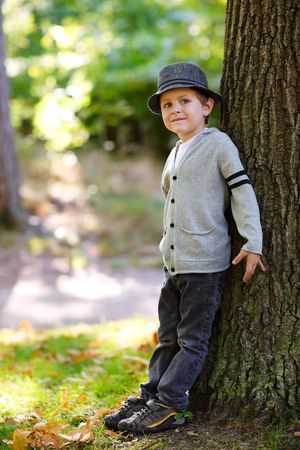 Stylish young boy in gray hat outdoors at autumn day