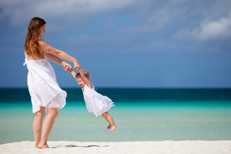 Young mother and her little daughter having fun on tropical white sand beach