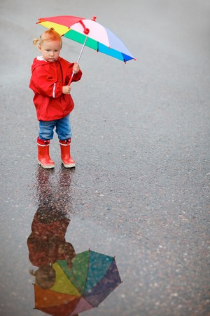 Toddler girl with colorful umbrella, beautiful reflection on puddle