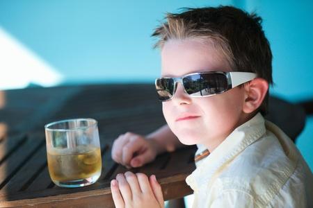 Portrait of stylish little boy in sun glasses drinking apple juice
