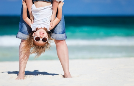 Photo pour Mother holding her happy smiling daughter upside down having beach fun - image libre de droit