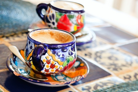 Cappuccino in traditional colorful mexican pottery cups