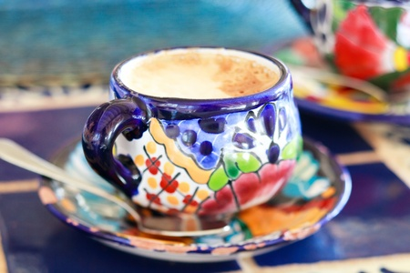 Cappuccino in traditional colorful mexican pottery cup