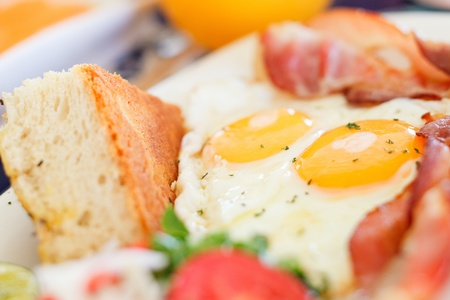 Delicious fried eggs with bacon and vegetables served for breakfast