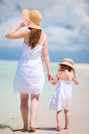 Foto de Back view of mother and daughter walking on beach - Imagen libre de derechos